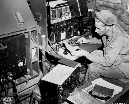 BC-342 radio receiver seen at bottom center, in use by Signal Corps operator in New Guinea. Photograph was taken by the U.S. Army Signal Corps, photo number: GHQ SWPA SC 43 5901 by T/4 Harold Newman.